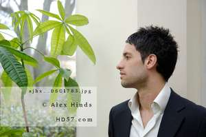 Thoughtful young man looking out of window with houseplant